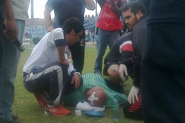 Luìs Mario Sperdutti en el piso a la espera de la ambulancia que lo retiró del estadio.